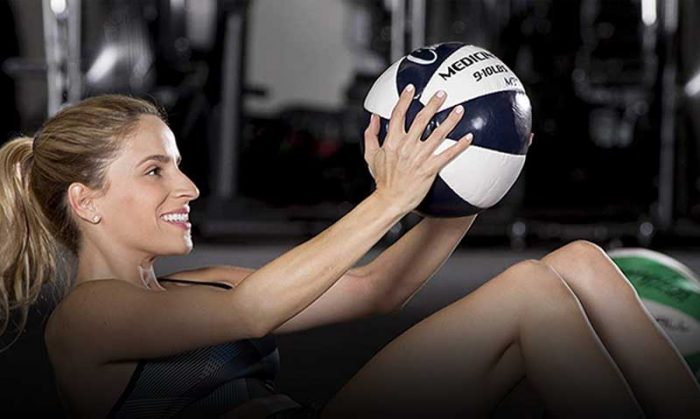Woman training abs with medicine ball